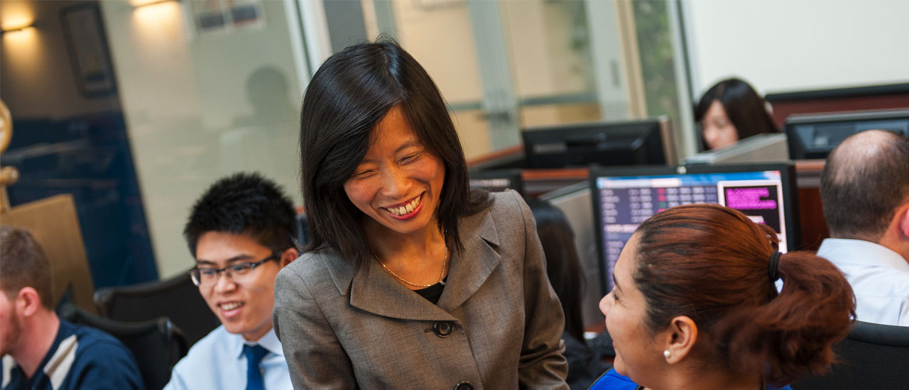 Eleanor Xu in Trading Room with two students