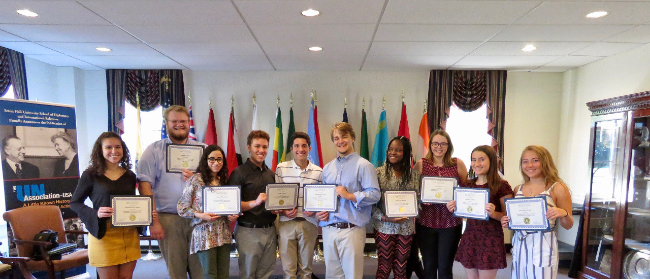 Students from the International Relations Summer Institute holding up their certificates in the Diplomacy room.