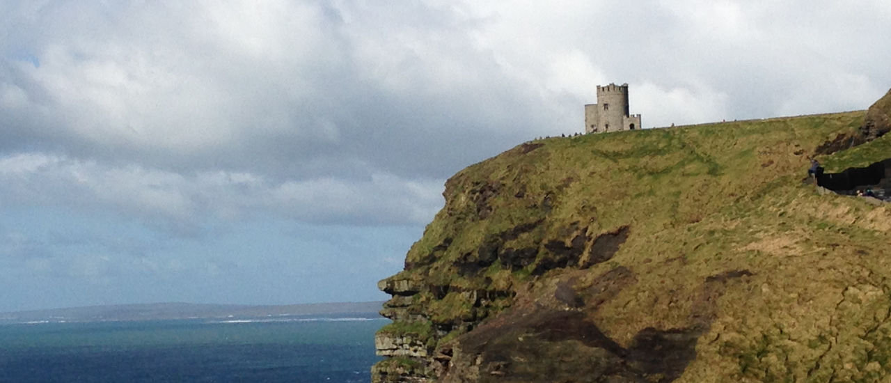 Irish coast with a castle on a cliff overlooking the water.