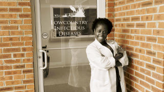 Nya Huguette Ebama '01 in a white coat.