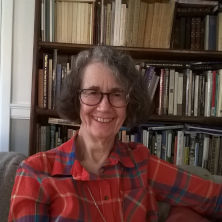 Celia Deutsch wearing a red flannel, sitting in front of a bookcase