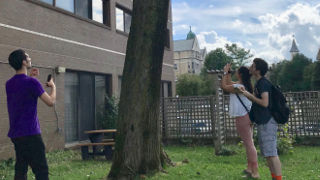 Photo of students taking picture of a tree