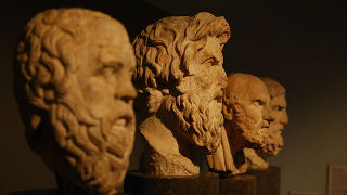 An image of three statues of philosophers.