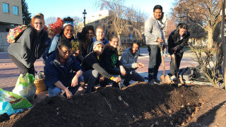 Students from the Environmental Studies program planting flowers on campus for peace.