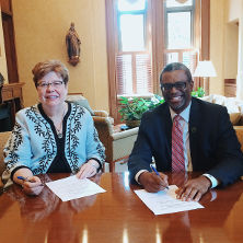 Seton Hall University Interim President Mary J. Meehan and Essex County College President Anthony E. Munroe sign an articulation agreement.
