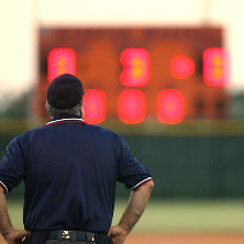Umpire looking at Baseball Scoreboard