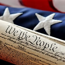 A picture of the US Constitution and the US Flag