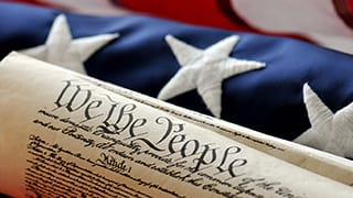 A picture of the US Constitution with the US Flag