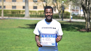 "Alphayaya Barrie holding up a sign that reads ""I'm ready to uphold the standard worldwide."""