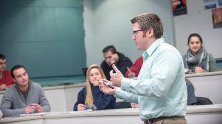 Professor addressing a group of students in a business class.