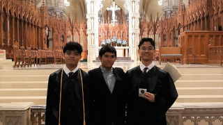 Three young males smiling for a photo in a church