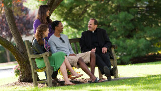Students sitting on a bench and talking with Fr. John.