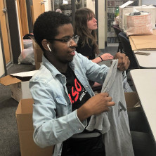 A student from the WSOU 89.5 FM station is sitting down at a table folding one of the grey shirts donated to the clothing drive. There is another student behind him also helping to organize the clothes. Around the students is boxes for the clothing drive.