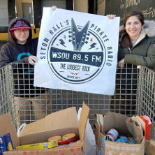 WSOU staff member Katherine Rossi and News Director Jocelyn Rogalo with some of the more than 350 pounds of food Seton Hall University's radio station collected during the station's annual food drive for the Community Foodbank of New Jersey.