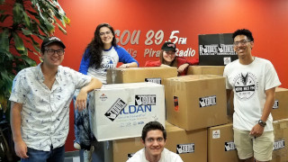 Five students are posed around boxes inside the WSOU 89.5 station containing items for the clothing drive.