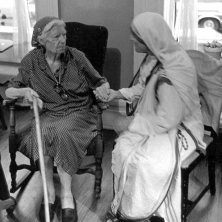 Dorothy Day and Mother Teresa sitting down and holding hands.