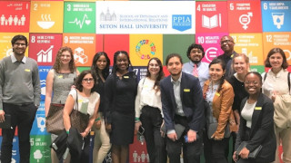 Students who attended the PPIA conference standing in front of a colorful wall depicting different aspects of international relations. Directly behind them in the center is a sign for the Seton Hall's International Relations and Diplomacy School.