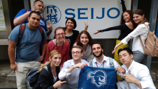 Students who participated in the Study Abroad program in Tokyo, Japan. The students are holding up a Seton Hall flag in the photo.
