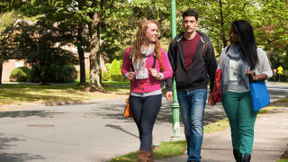 Three students walking off campus