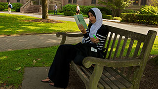 A Seton Hall Student Sitting on a Bench Reading