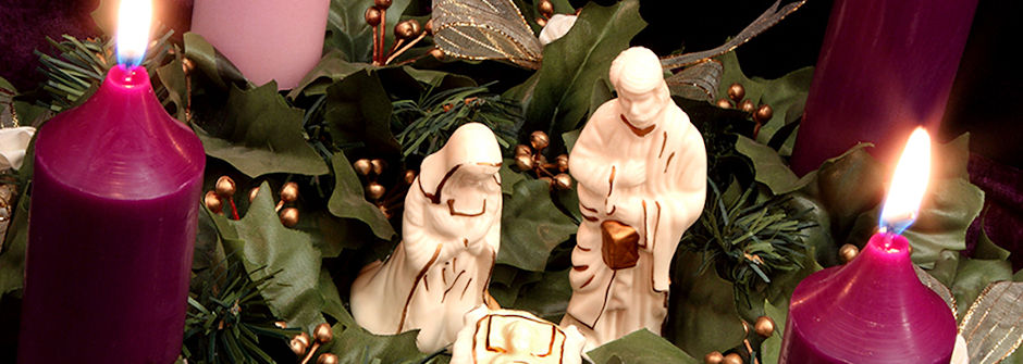 Lit advent candles with angle statues.