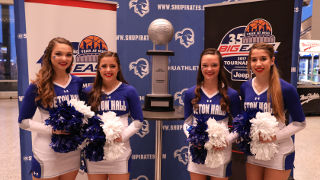 Cheerleaders posing with the BIG EAST Trophy.