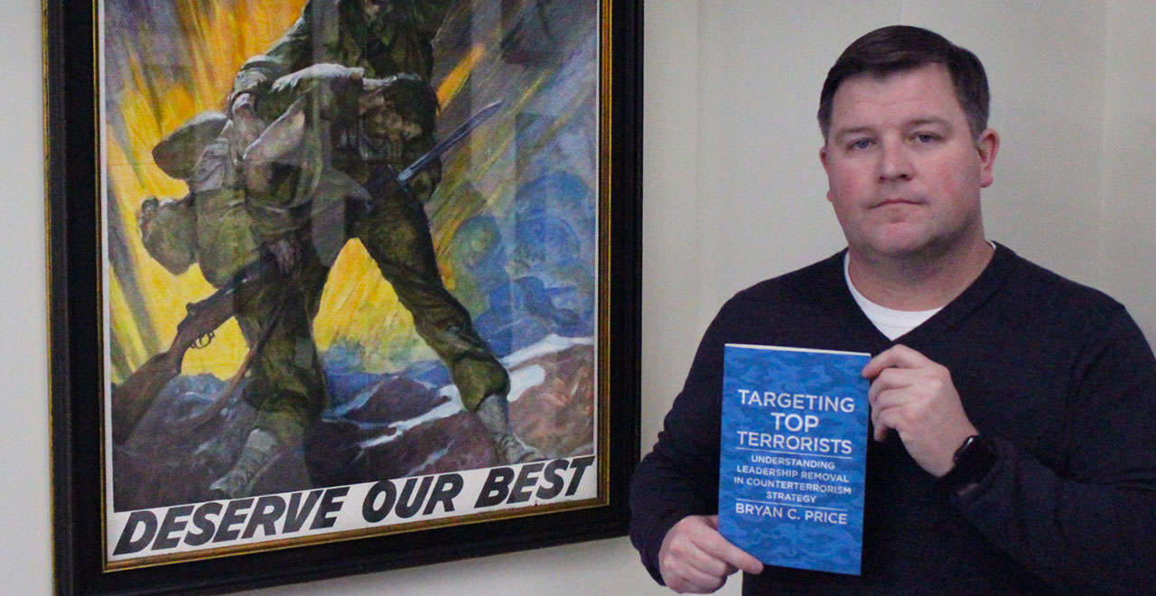 Lieutenant Colonel (Retired), U.S. Army, Bryan C. Price, Ph.D., standing next to an army poster holding his new book, Targeting Top Terrorists