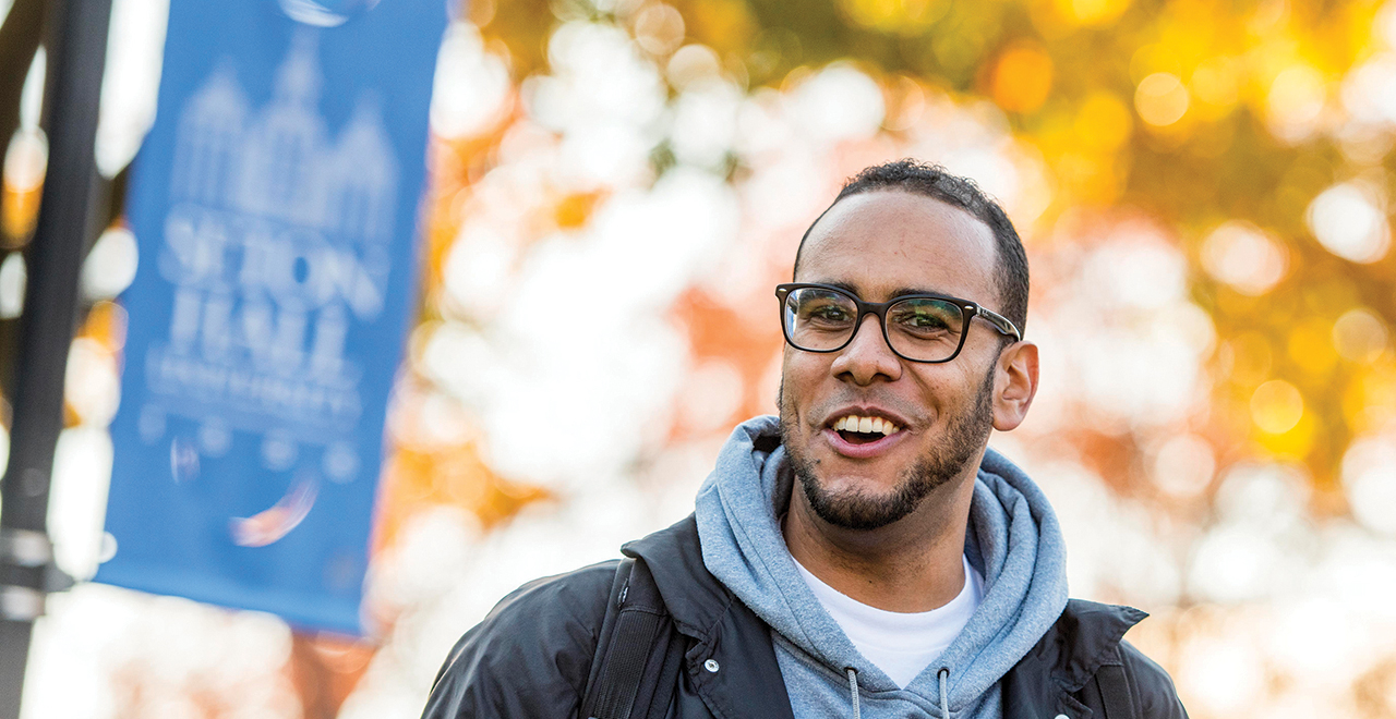 A College of Education Student Standing on Campus in Front of a Seton Hall Banner in Autumn
