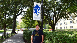 Incoming freshman, Connor Hester, in front of a Seton Hall sign.
