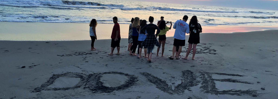 "Students on the beach with the word ""DOVE"" spelled out in the sand."