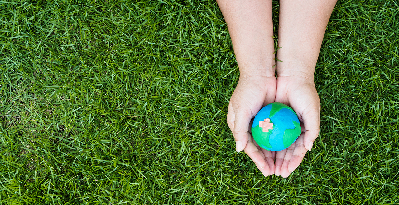 A photo of hands holding a model of the globe over a field of grass.