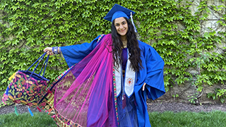 College of Education Student in her cap and gown on campus.