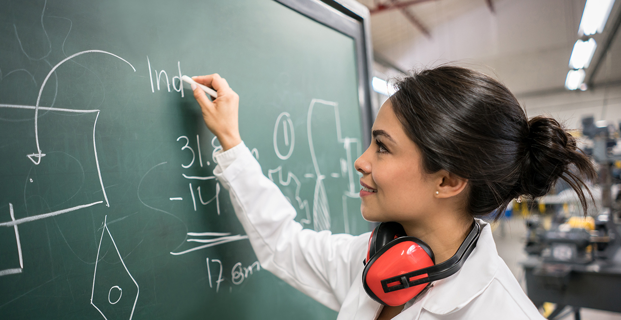 A female engineering student working on equations on a chalk board.