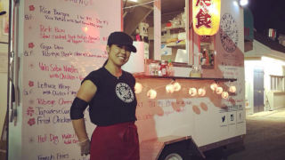 Girl in hat and apron standing in front of a food truck