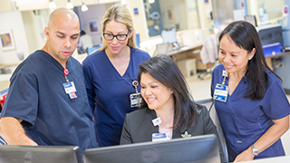 Group image of nurses at a hospital, starring at a computer screen.