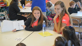 Student athletes reading to children