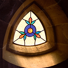 Stain glassed window with light shining through it.