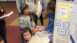 Anne Pino (rightmost) impresses a young participant as her LED light shines blue.