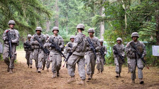 Soldiers with guns walking in the woods.