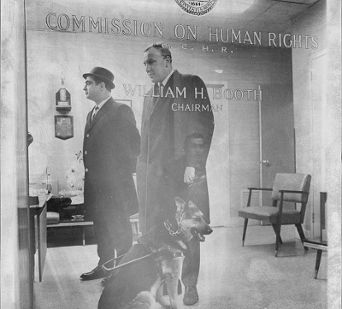 Edwin R. Lewinson and his seeing eye dog in the office of the Commission on Human Rights.