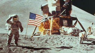 Neil Armstrong next to an American flag on the moon