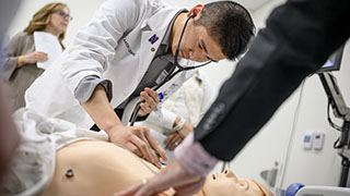 A male medical school student working in the simulation lab