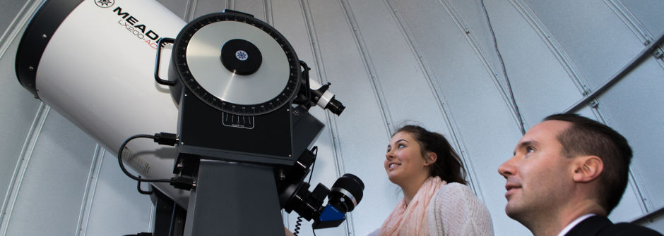 Student and Father Laracy looking through a telescope in the observatory.