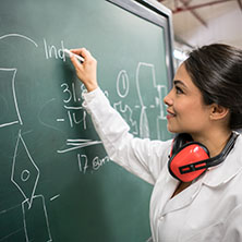 A female engineering student working on a chalk board figuring out a physics equation.