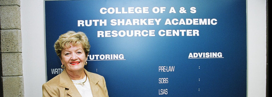 Ruth Sharkey in front of the Ruth Sharkey Academic Resource Center sign.