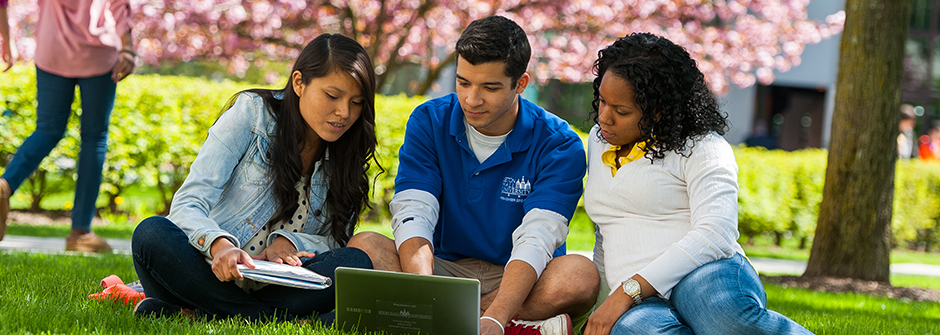Three students looking at a laptop outside.
