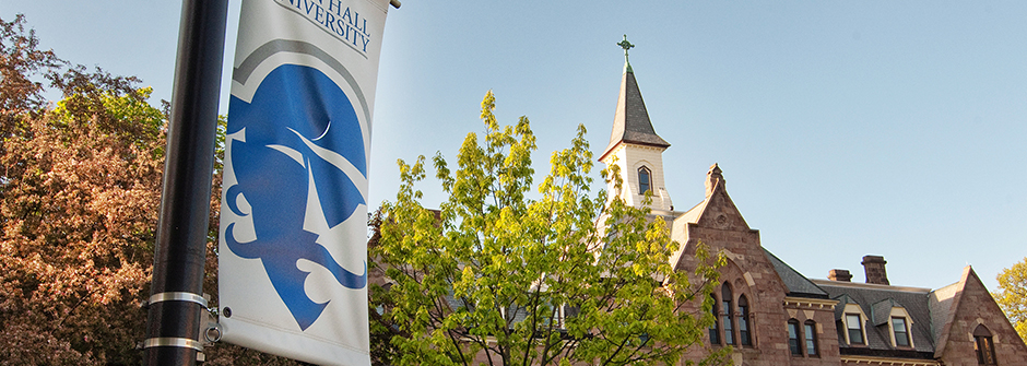 Seton Hall pole banner with President's Hall in the background.