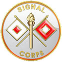 The Signal Corps seal is a white circle with a golden torch in the center with red and white flags crossed behind it