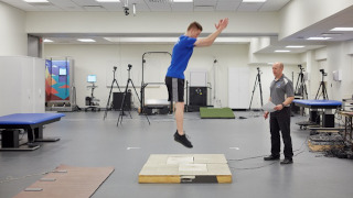 Student jumping on a mat.