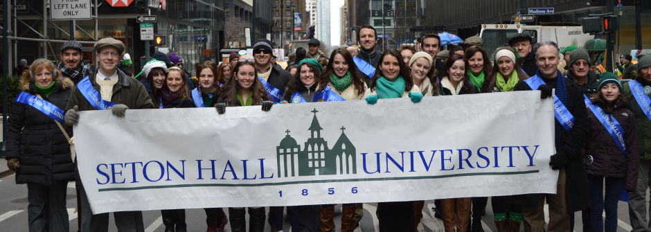 Members of the Seton Hall community in the streets of New York City holding up a banner at the St. Patrick's Day Parade.